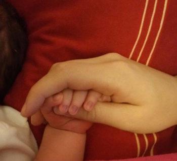 Erste zärtliche Berührung von Mutter und Babys Händen im Geburtshaus.