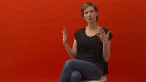 """Mutter aus dem Film """"Meine Narbe"""" sitzt vor rotem Hintergrund und spricht über ihre Kaiserschnitterfahrung"""